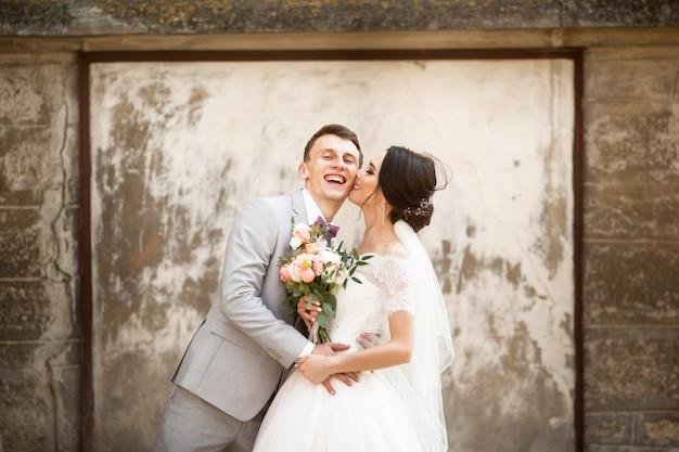 Lindo casal de noivos beijando perto da antiga muralha