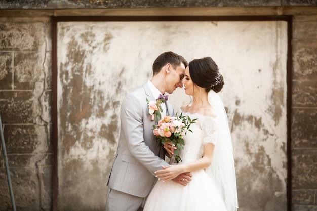 Lindo casal de noivos beijando perto da parede velha