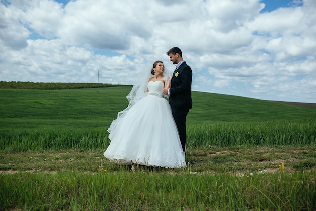 Lindo casal de noivos caminhando no campo verde
