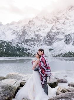 Lindo casal de noivos coberto com manta brilhante está de pé na frente do lago congelado, rodeado por montanhas nevadas