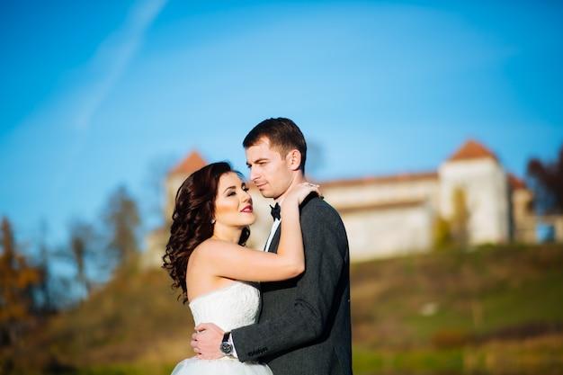 Lindo casal de noivos elegantes felizes em uma caminhada no parque ensolarado de verão ou no jardim no dia do casamento