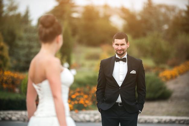 Lindo casal de noivos em pé frente ao outro no parque