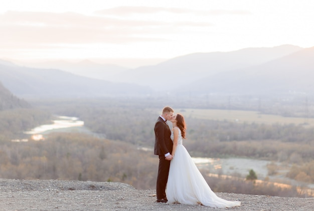 Lindo casal de noivos está beijando na colina com vista para uma paisagem pitoresca ao entardecer