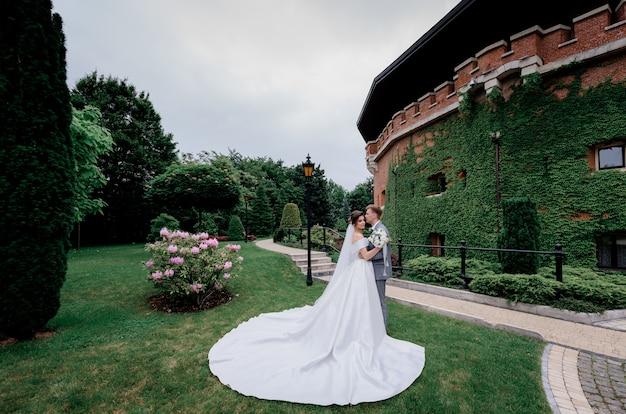 Lindo casal de noivos está de pé no parque verde perto do edifício totalmente coberto de folhas