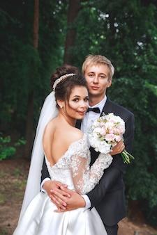Lindo casal de noivos no parque. noiva e noivo se abraçam ao ar livre