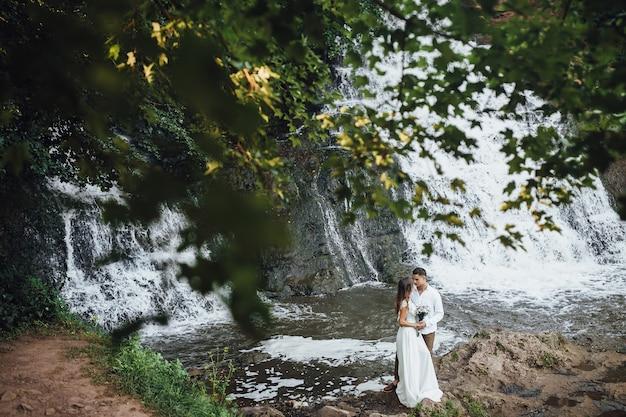 Lindo casal de noivos perto de cachoeira.