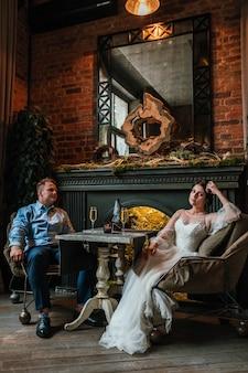 Lindo casal de noivos posando em um restaurante, recém-casados sentam-se perto da lareira e de mãos dadas, o conceito é uma nova família, um lindo casamento.