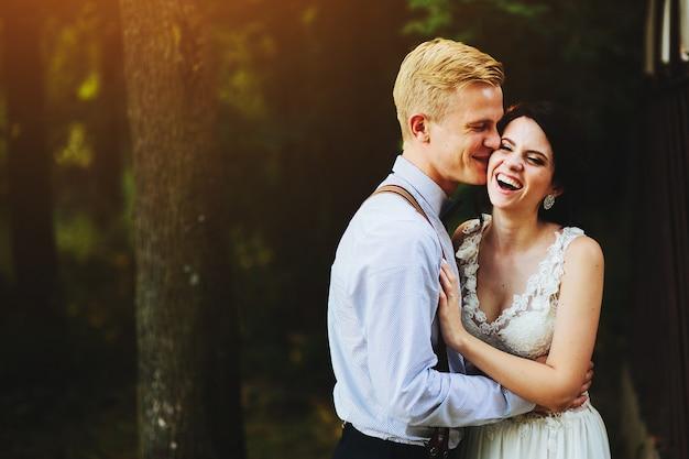 Lindo casal de noivos posando em uma floresta