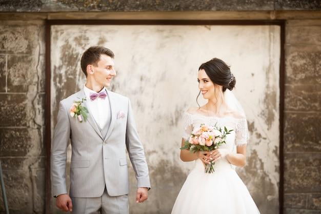 Lindo casal de noivos posando perto da parede velha