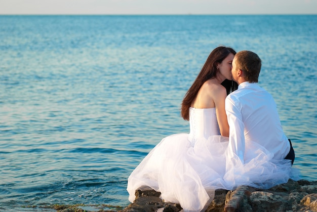Lindo casal de noivos se beijando na praia