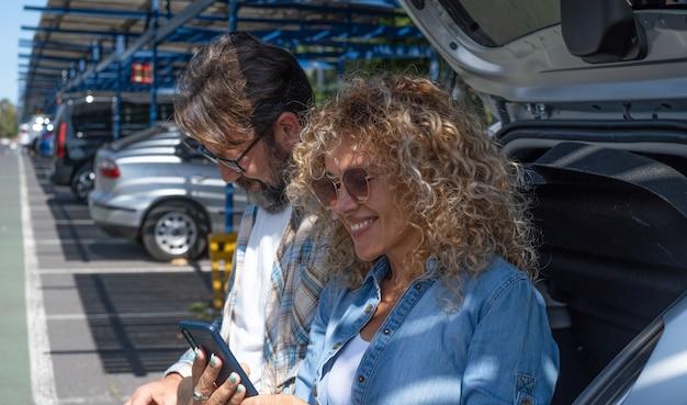 Lindo casal de turistas no estacionamento do aeroporto olhando para um telefone inteligente esperando o voo