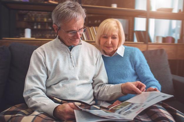 Lindo casal de velhos estão sentados juntos no sofá e lendo