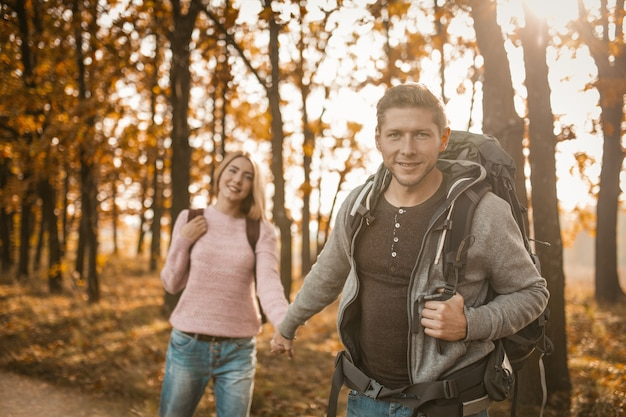 Lindo casal de viajantes a pé ao longo de uma trilha na floresta