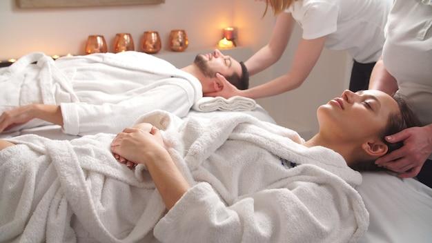 Lindo casal deitado em camas de massagem, desfrutando de uma massagem na cabeça em spa de luxo.