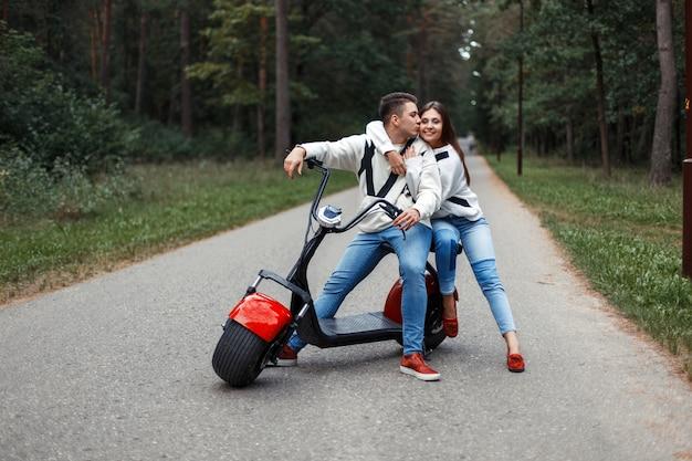 Lindo casal elegante com roupas jeans com uma bicicleta elétrica vermelha na floresta.