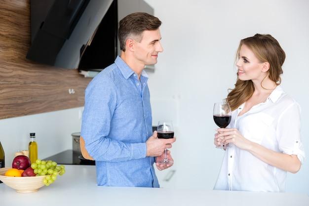 Lindo casal em pé e bebendo vinho tinto na cozinha de casa