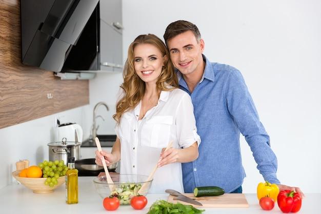 Lindo casal em pé e cozinhando na cozinha de casa