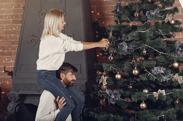 Lindo casal em pé em casa perto da árvore de natal