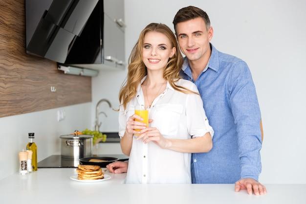 Lindo casal em pé na cozinha com panquecas e suco de laranja fresco no café da manhã