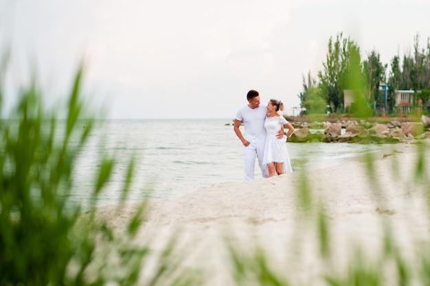 Lindo casal em roupas brancas, caminhando no mar