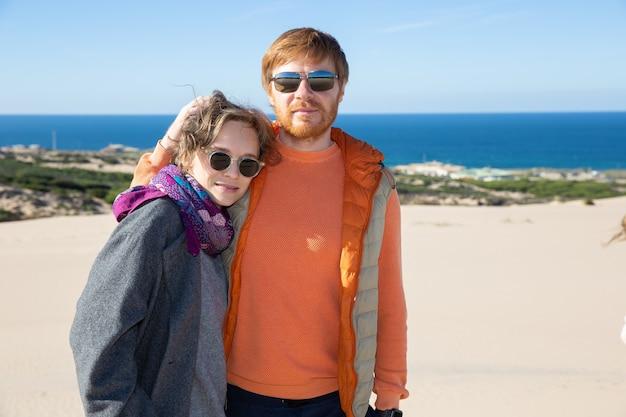 Lindo casal em roupas quentes, passando momentos de lazer no mar, em pé na areia, se abraçando, olhando para a frente