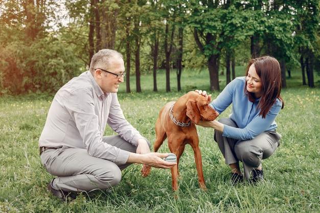 Lindo casal em uma floresta de verão com um cachorro