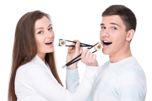 Lindo casal está comendo sushi