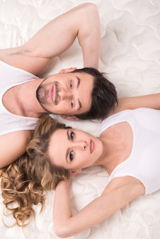 Lindo casal está deitado sobre o colchão de qualidade.