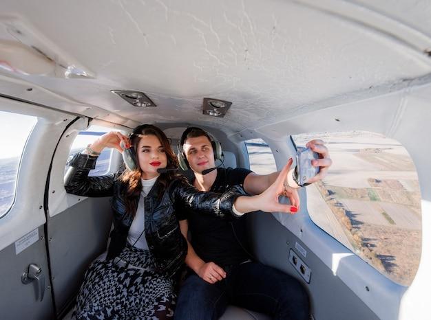 Lindo casal está fazendo selfie dentro de helicóptero com paisagens de tirar o fôlego pela janela