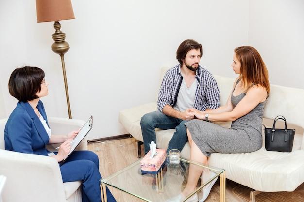Lindo casal está sentado juntos. homem e mulher estão olhando um para o outro. eles são muito sérios e tristes. o psicólogo está sentado na frente deles e olhando para eles.