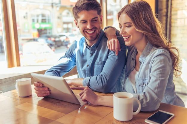 Lindo casal está usando um tablet, conversando e sorrindo.