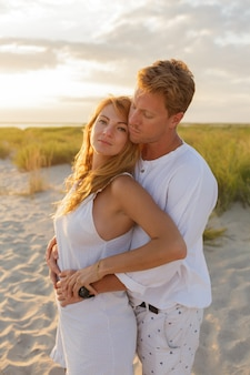 Lindo casal europeu abraçando contra o pôr do sol na praia.
