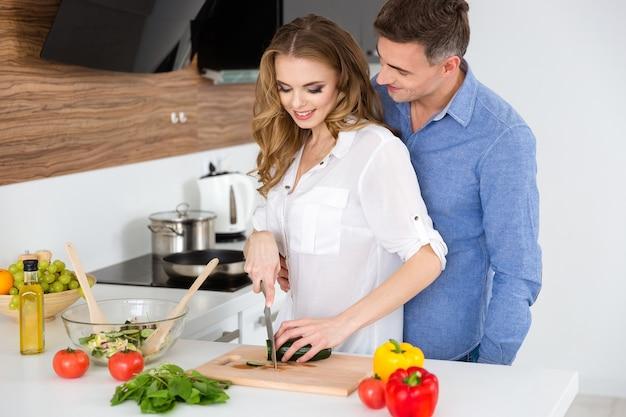 Lindo casal fazendo salada vegetariana e flertando na cozinha