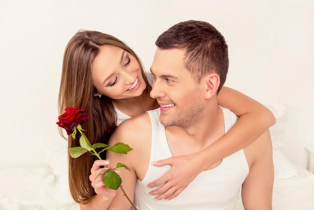 Lindo casal feliz apaixonado, abraçando e segurando uma rosa vermelha