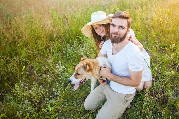 Lindo casal feliz com seu cachorro alabai na natureza com o pôr do sol.