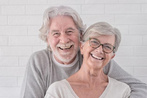 Lindo casal feliz de duas pessoas idosas se abraçando - em pé se divertindo em casa - conceito de aposentadoria serena