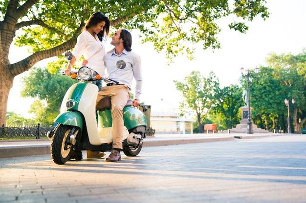 Lindo casal feliz flertando em uma scooter