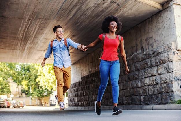 Lindo casal feliz multicultural correndo na rua.