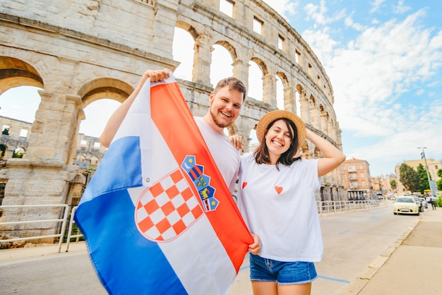 Lindo casal feliz na frente do coliseu em pula croácia com bandeira croata. conceito de viagens
