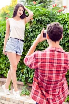 Lindo casal feliz perto de uma parede verde em estilo casual com câmera