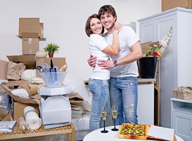 Lindo casal feliz se abraçando em seu novo apartamento