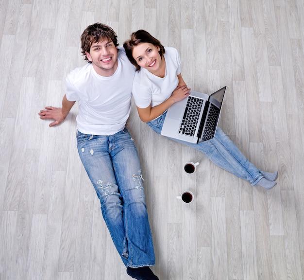 Lindo casal feliz sentado no chão em uma nova casa com um laptop