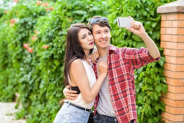 Lindo casal feliz tirando uma selfie em um celular se abraçando e se divertindo juntos