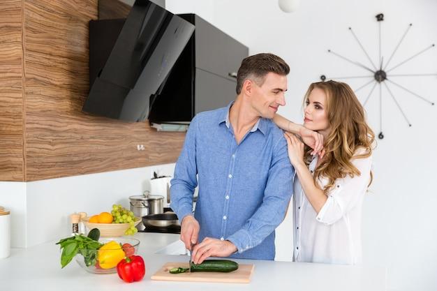 Lindo casal flertando e cortando legumes na cozinha de casa