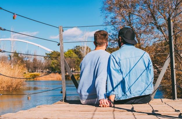 Lindo casal gay com máscara de mãos dadas, sentado na ponte de madeira com cadeados, olhando para o lago