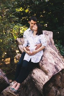 Lindo casal grávida relaxante lá fora na floresta