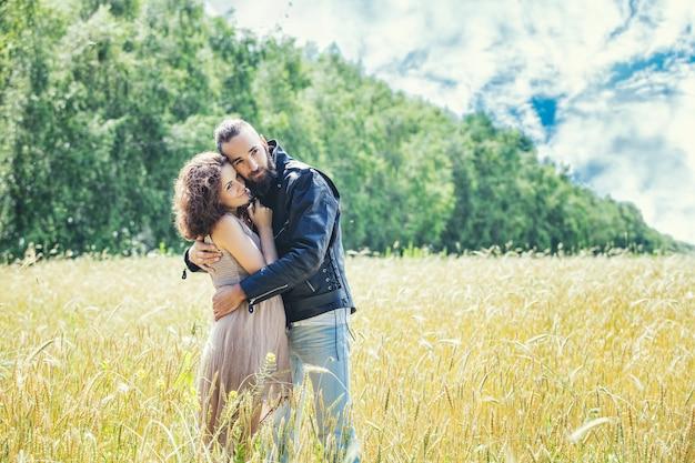 Lindo casal homem e mulher apaixonados no campo contra o céu feliz