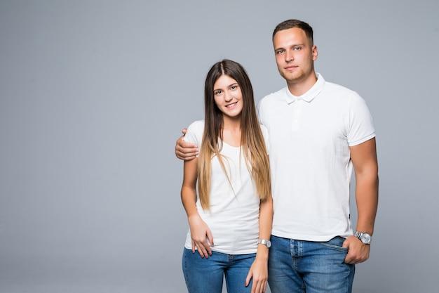Lindo casal, homem e mulher em camiseta branca, sorrindo isolado em um fundo cinza