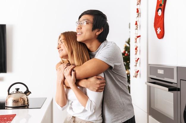 Lindo casal, homem e mulher, em pé na cozinha bem iluminada e se abraçando