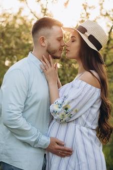 Lindo casal, homem e mulher grávida em grinalda de flores na cabeça, abraçando no jardim primavera. mãe feliz esperando bebê!